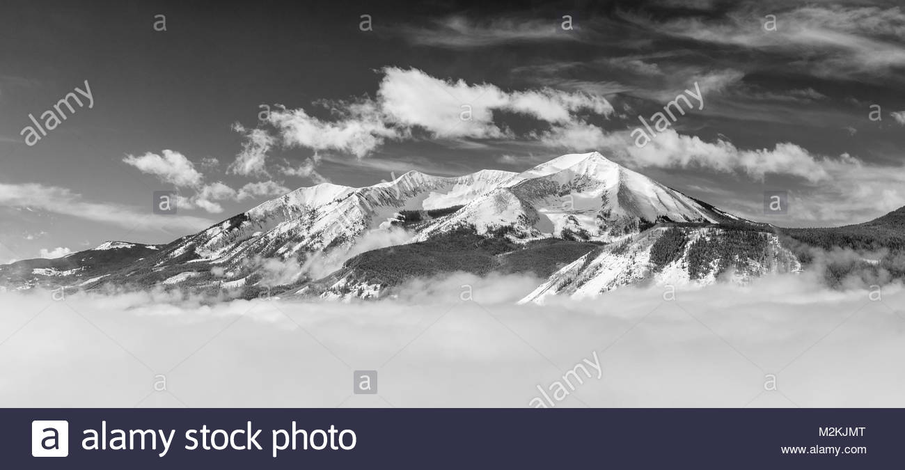 Whetstone Mountain near Crested Butte, Colorado rises from a sea of spring fog. - Stock Image