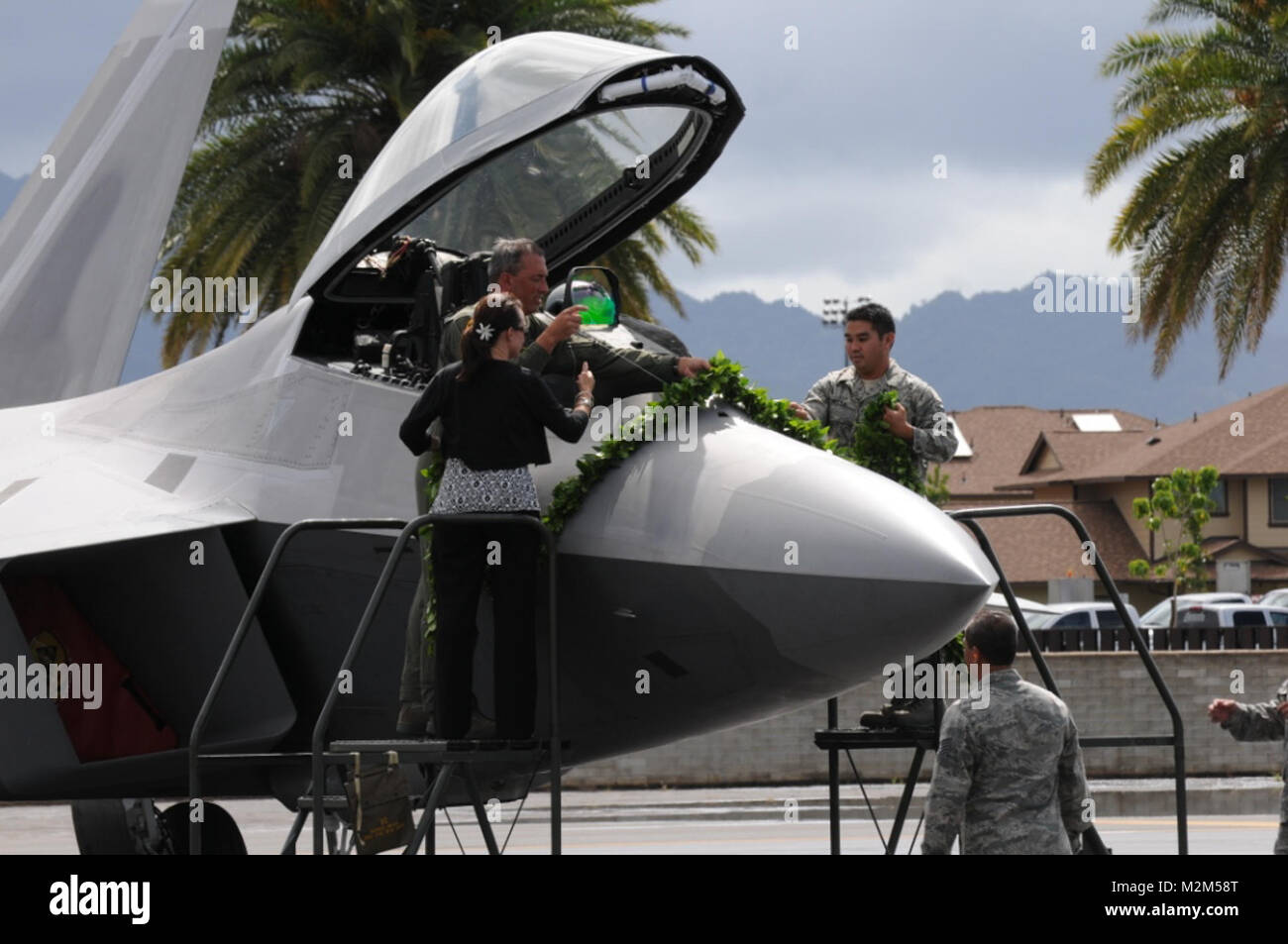 Lt Col Christopher Faurot, his spouse and SSgt Ben Nitta drape the Maile lei over the F-22 to commemorate the significant - Stock Image