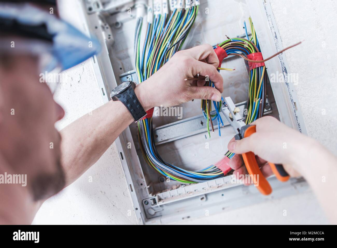 Electrical System Installation by Professional Caucasian Electrician. Construction and Power Industry Theme. - Stock Image