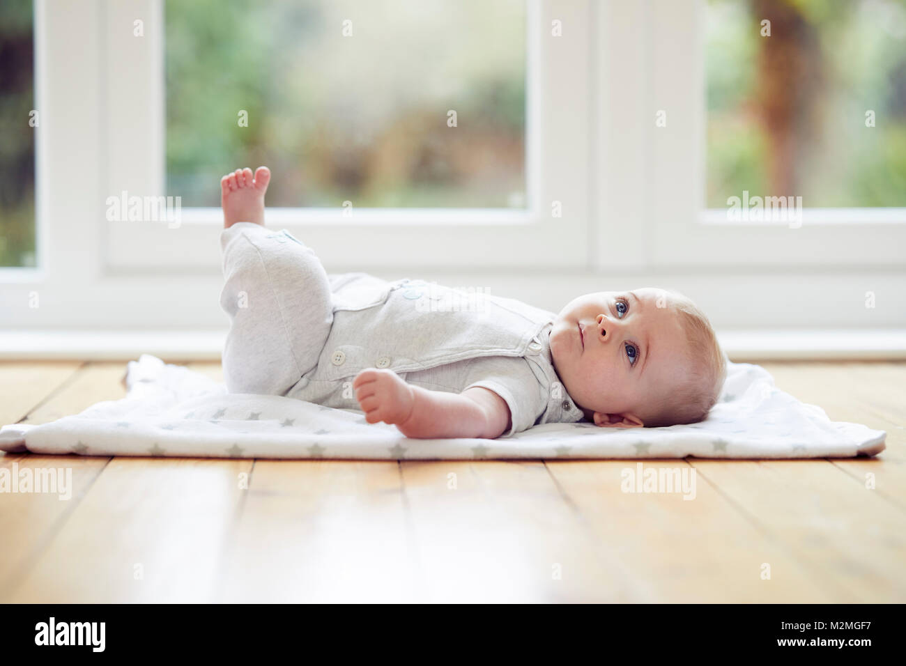 Baby laid on a matt - Stock Image