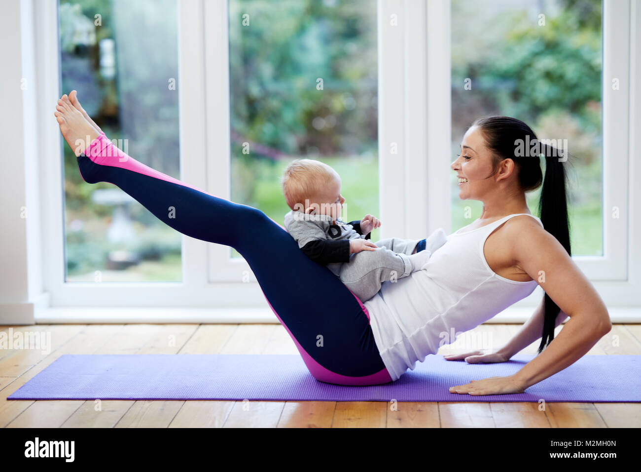 Mother exercising with her child Stock Photo