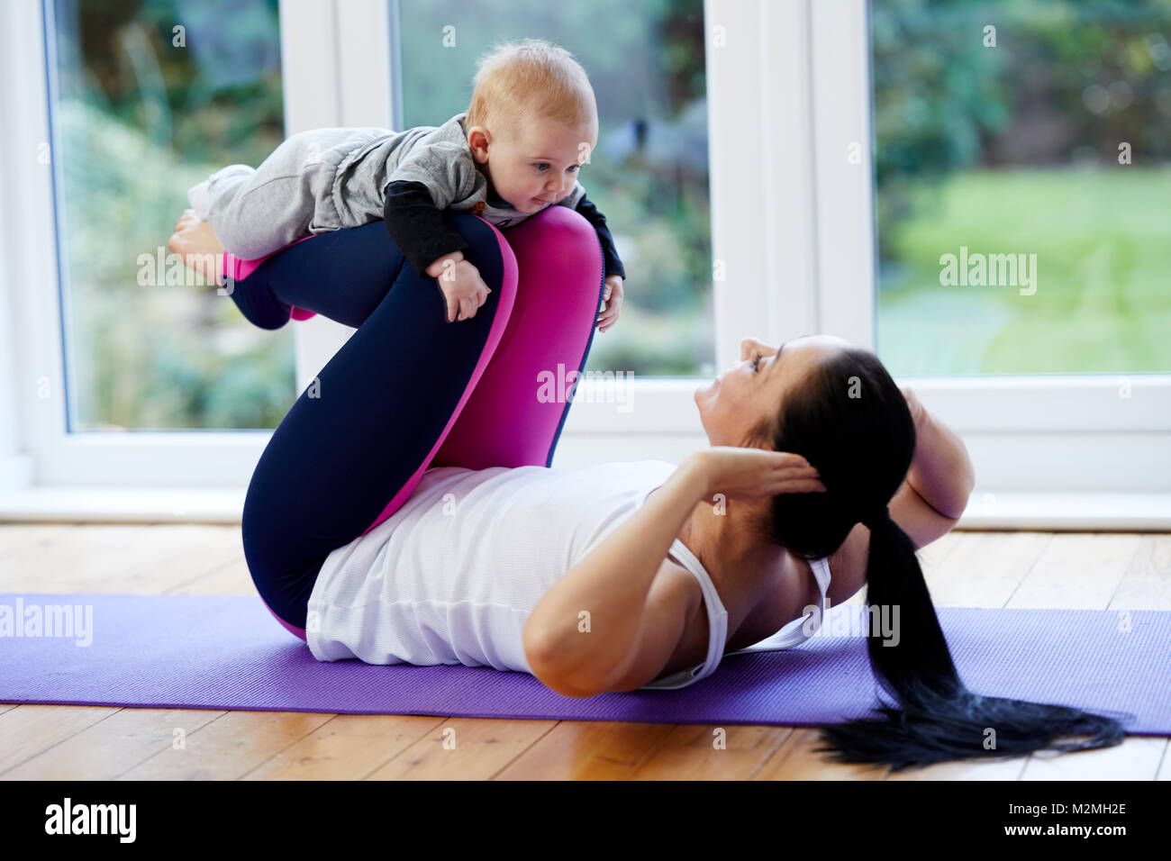 Mother exercising with her child - Stock Image