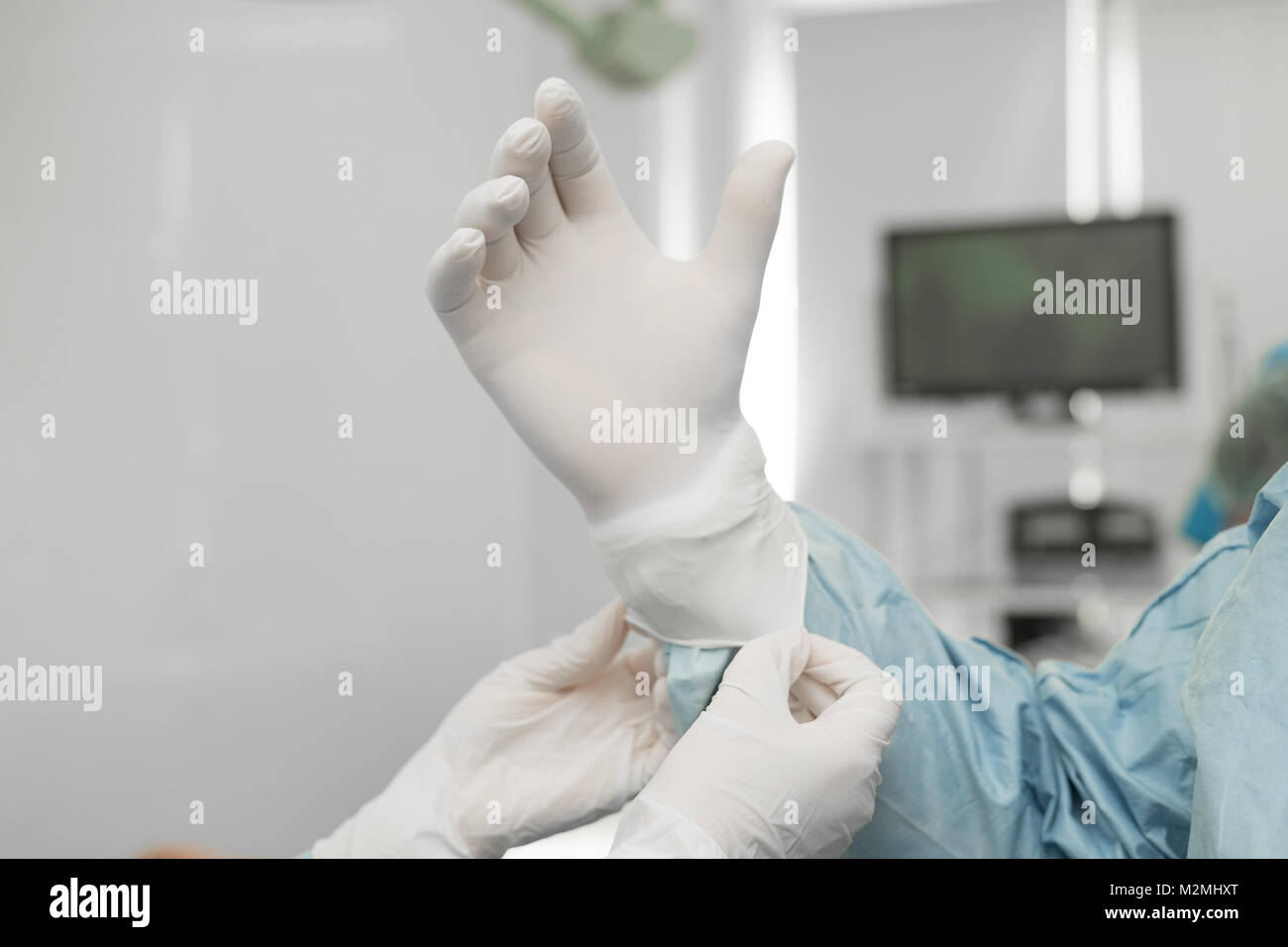 Surgeons are preparing for surgery. The assistant helps the experienced chief surgeon put on sterile rubber gloves. - Stock Image