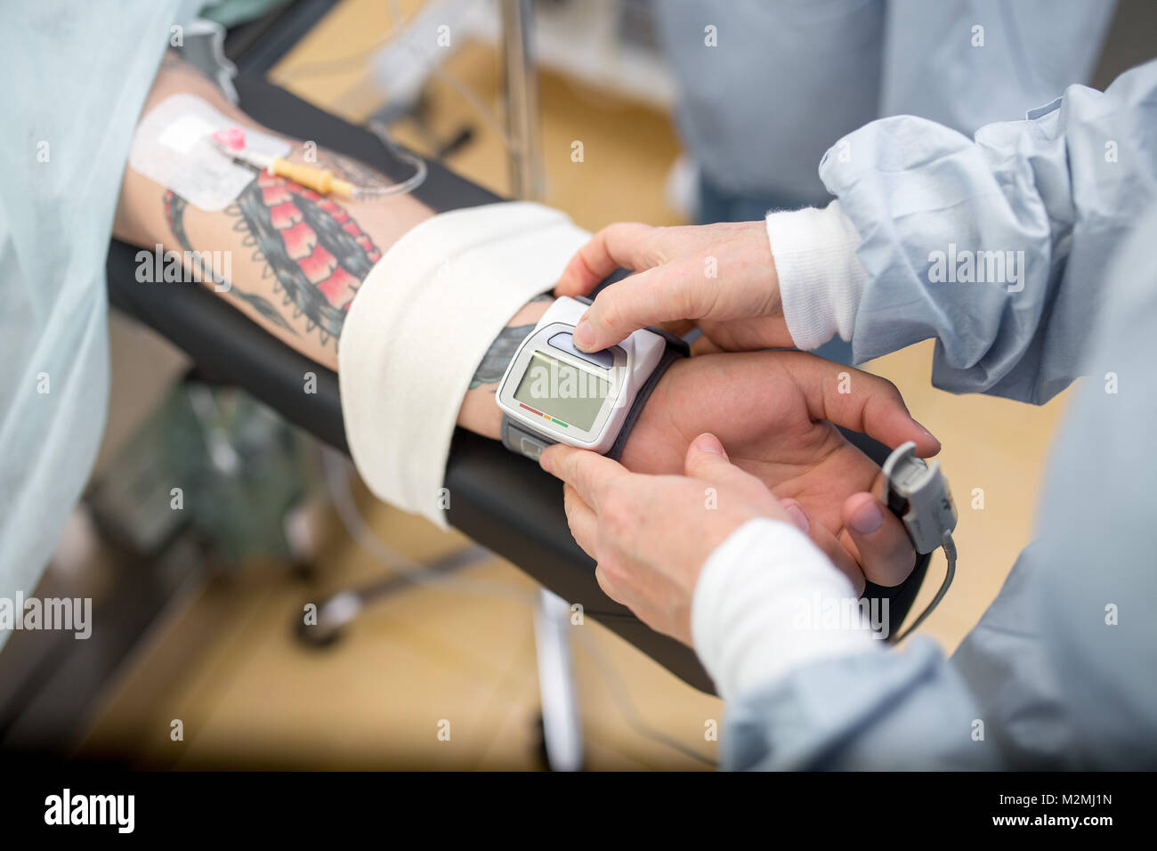 Doctor checking Blood Pressure of patient during surgery. medicine, surgery, resuscitation, emergency concept. Close - Stock Image