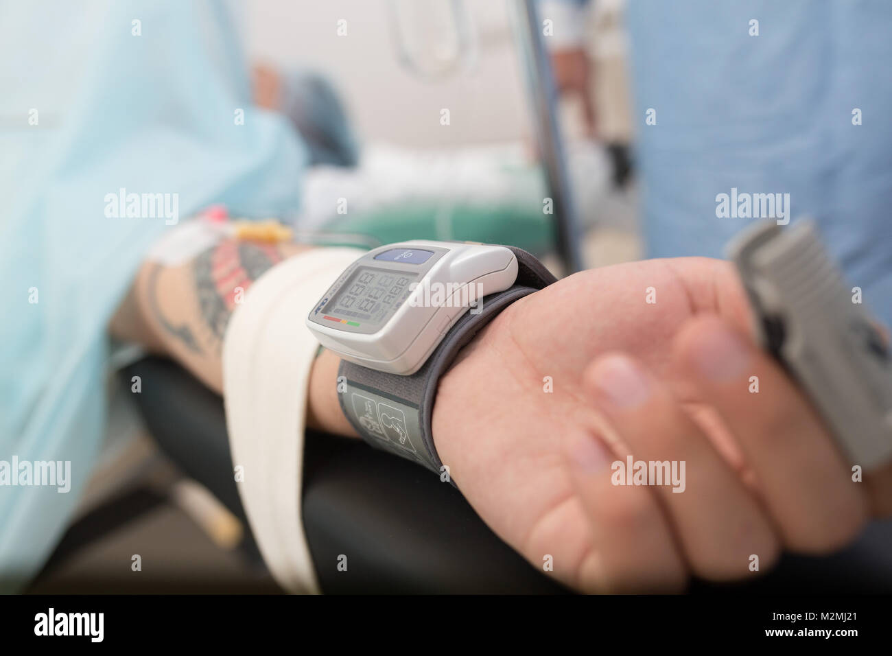 pulse oximeter on finger of patient during surgery. hand of male patient lying on the hospital bed with Digital - Stock Image