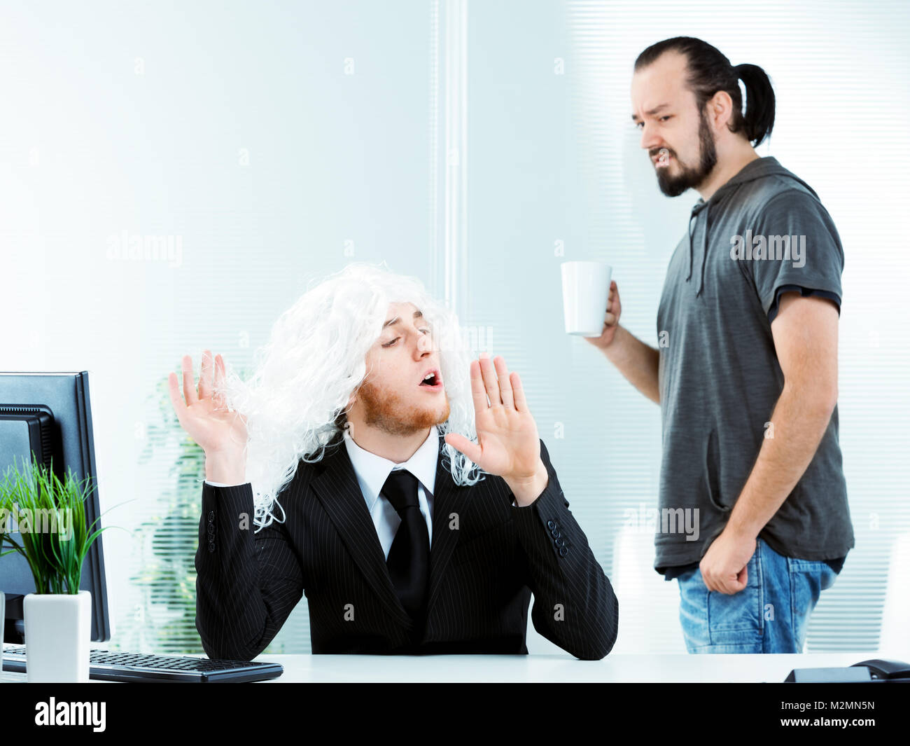 Affected narcissistic young businessman wearing a suit and white wig in the office gesturing with his hands watched - Stock Image