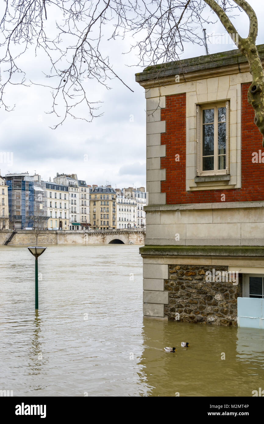 View of a brick house on the wharf of the Seine in Paris, half-submerged by the water during the flood episode of - Stock Image