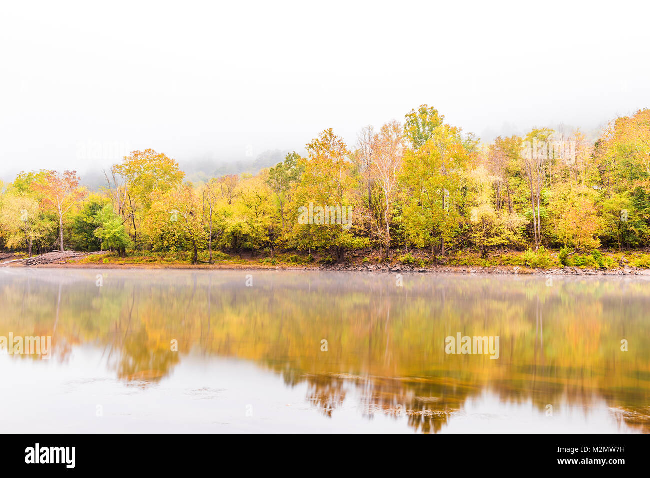 New River Gorge water river lake during autumn golden orange foliage in fall by Grandview with peaceful calm tranquil morning bright mist fog Stock Photo