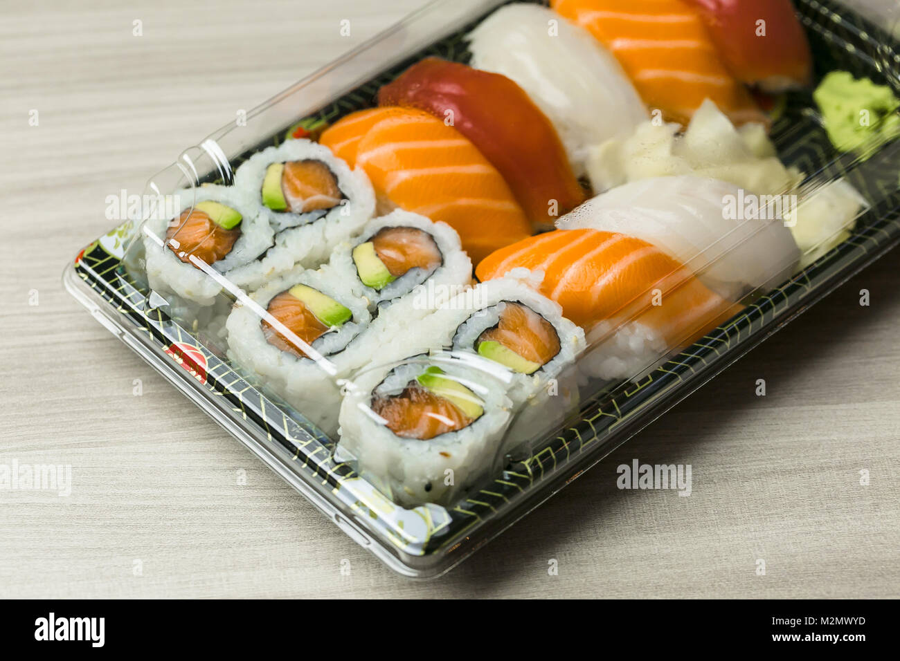 Takeaway food plastic containers for Sushi, Sashimi and Futomaki rolls.  Fresh made Sushi set with salmon, prawns, - Stock Image