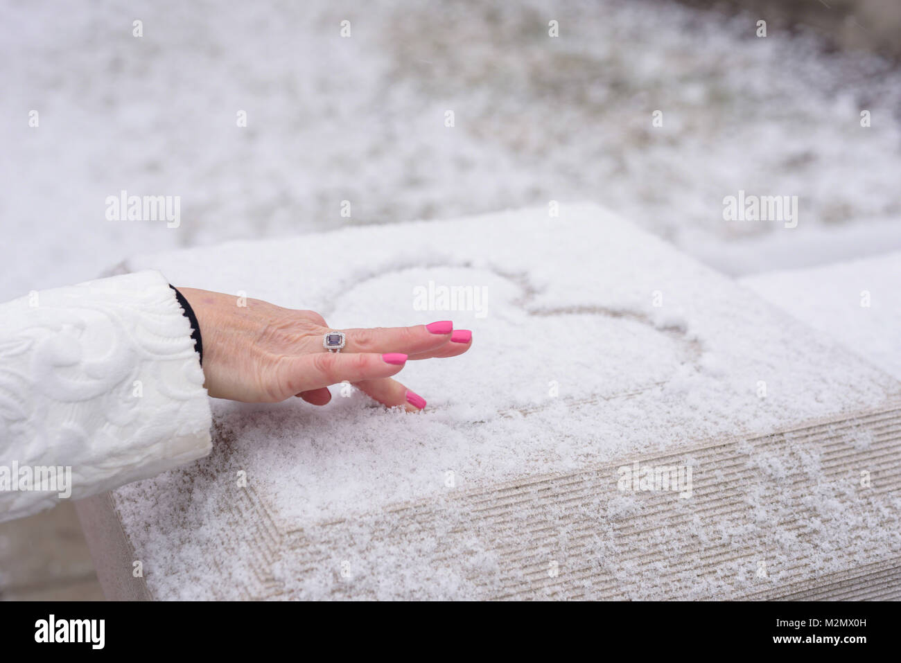 close up of a female hand drawing a heart in fresh snow with finger - Stock Image