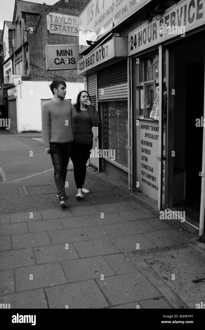 Black & White Photograph of a young couple walking past a cab office in Tooting, South London, England, United - Stock Image