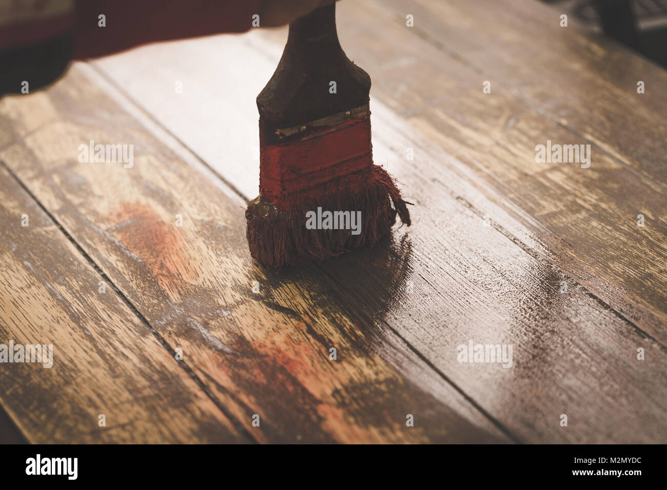 Craftsman hand painting brown color on wooden table use for home decorated. Wood renovation. Toned Image. - Stock Image