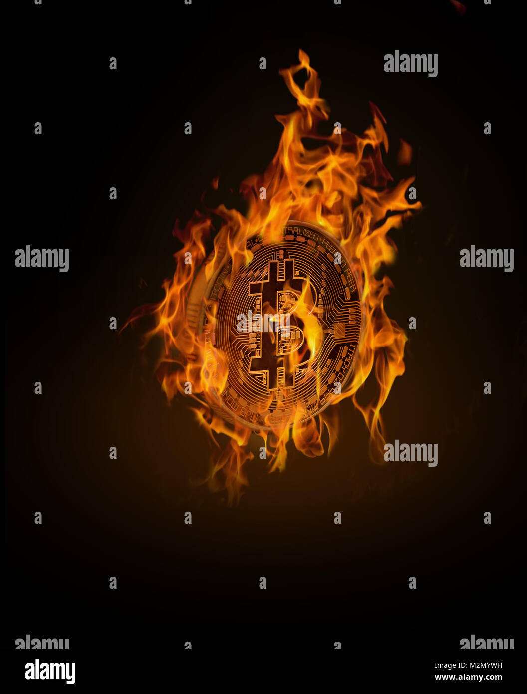 Burning gold bitcoin with flames on a black background - Stock Image
