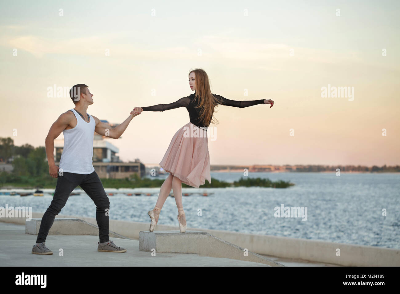 A slender ballerina and her boyfriend dance on the street. He holds her hand. She stands on tiptoe. - Stock Image