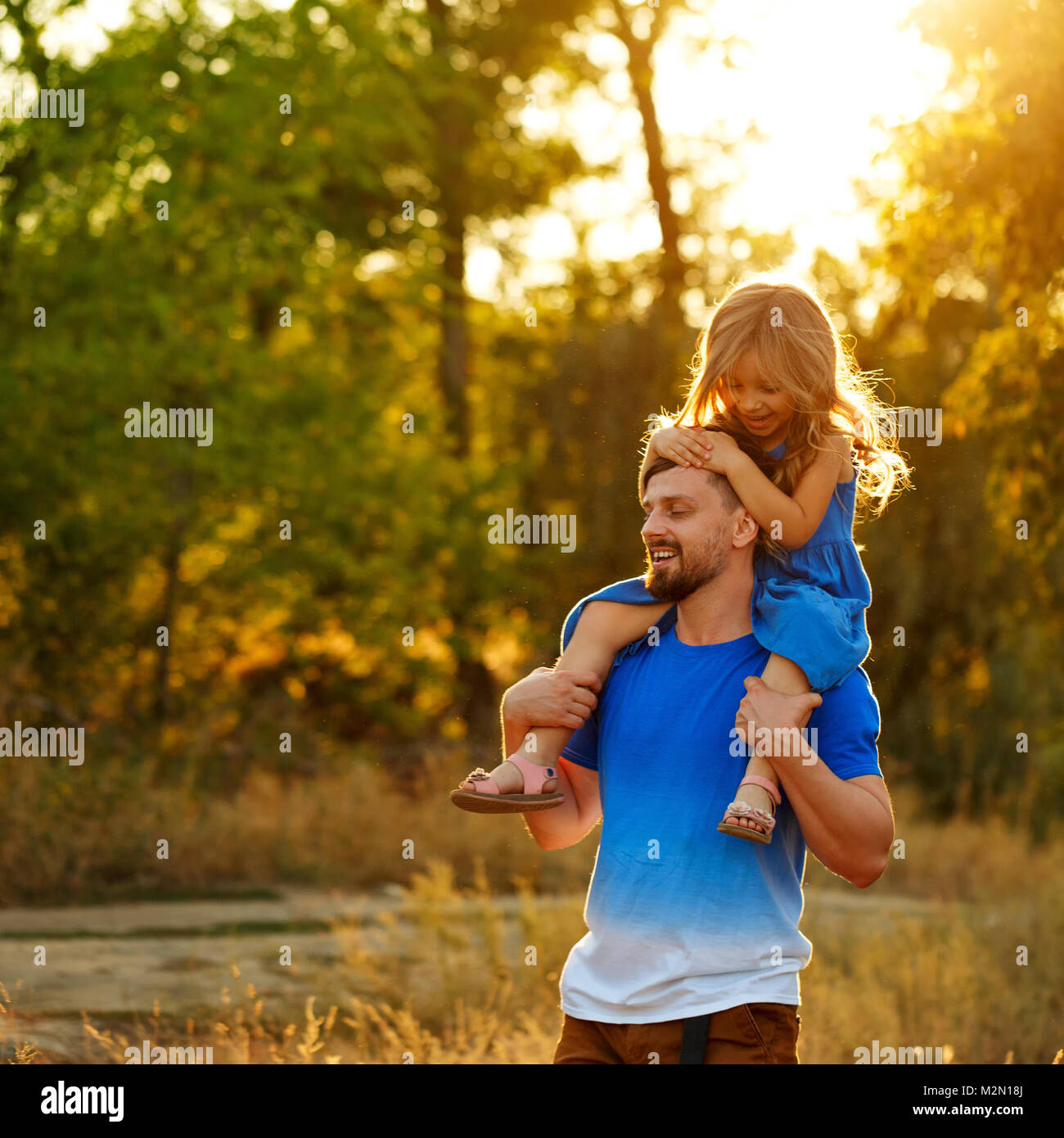 Family time. The father holds the daughter on the shoulders of piggyback. Walk in the park. They laugh and rejoice. - Stock Image
