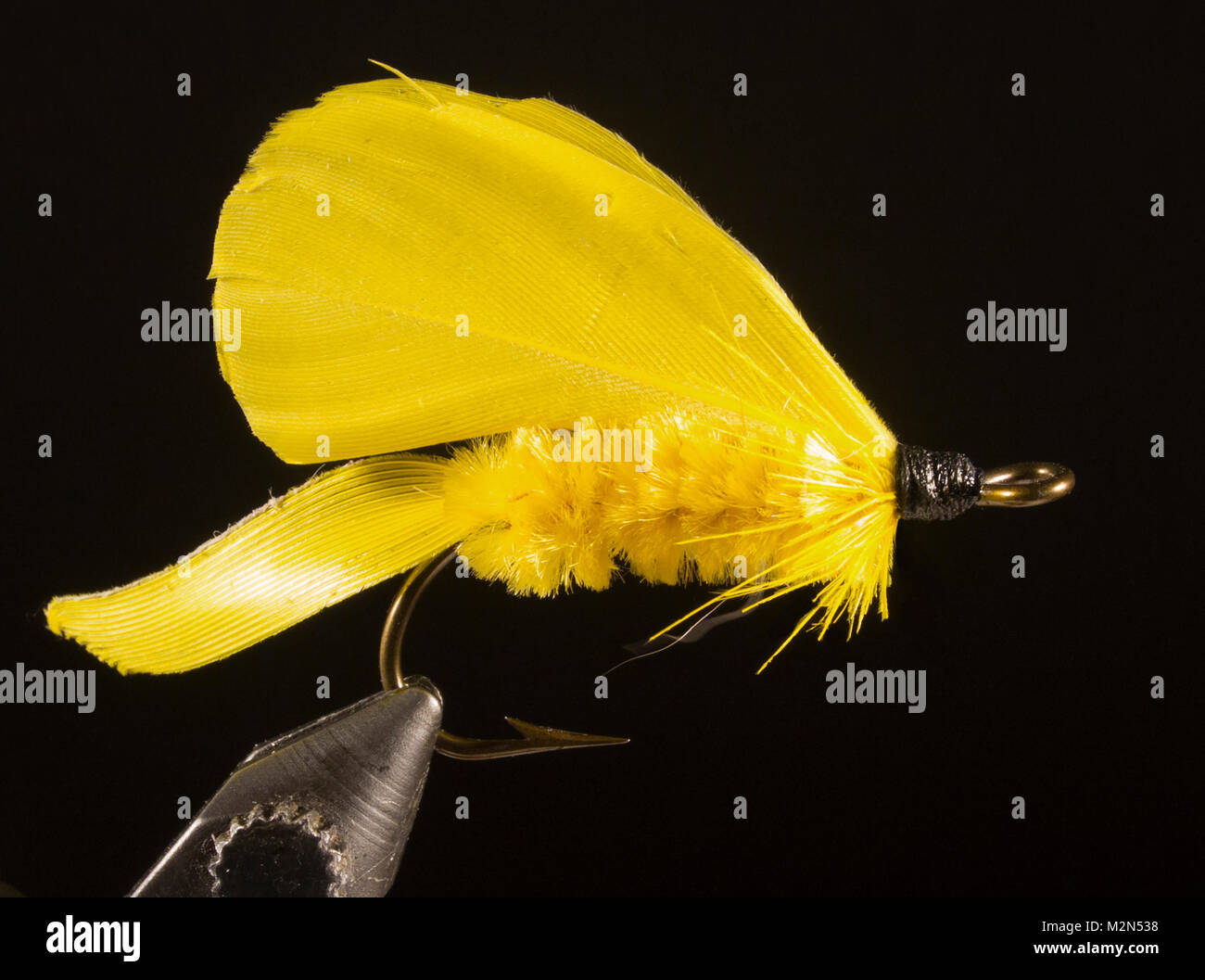 Yellow Chenille Bass Fly - unknown Hook: ring-eye bass hook. Size No.1 Tail: quill, dyed yellow Body: yellow chenille Stock Photo