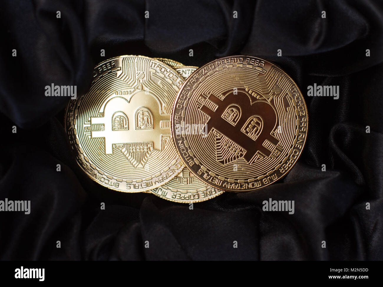 horizontal top view closeup of bitcoin golden metallic coins on black velvet background - Stock Image