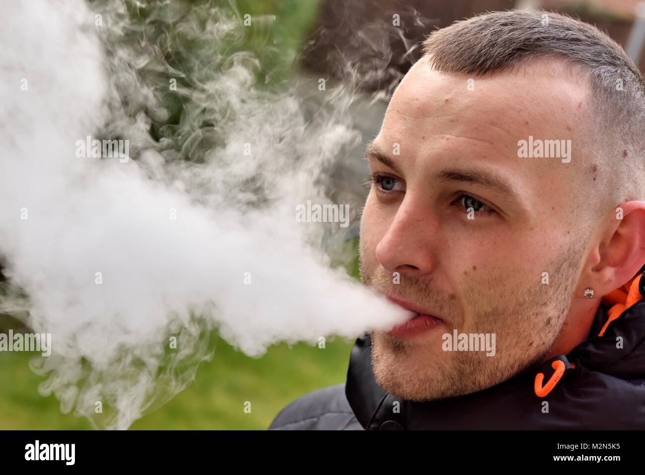A 27 year old man vaping smoke - Stock Image