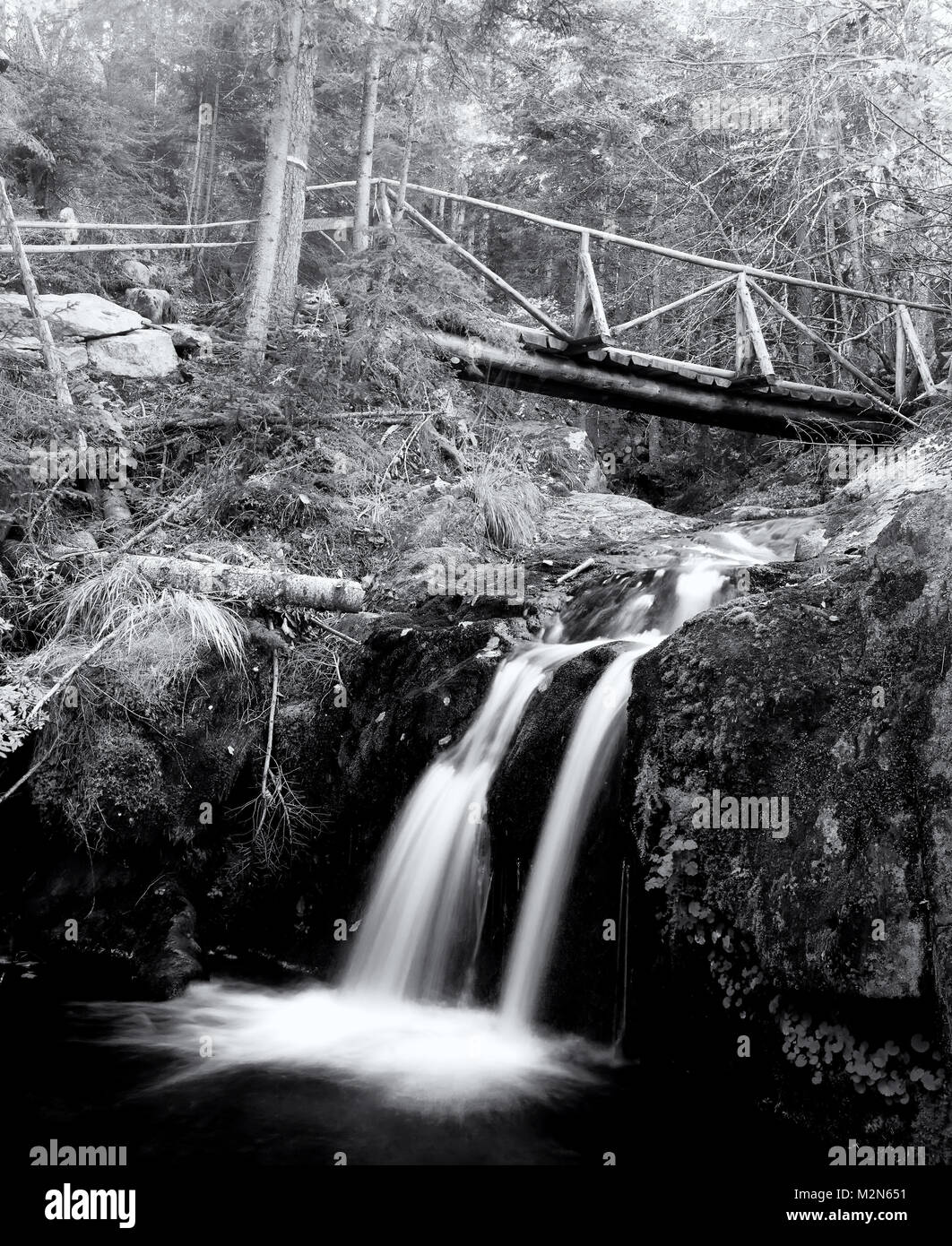 Waterfall cold fresh water stream long shutter speed blurred motion on black stone rocks in park - Stock Image