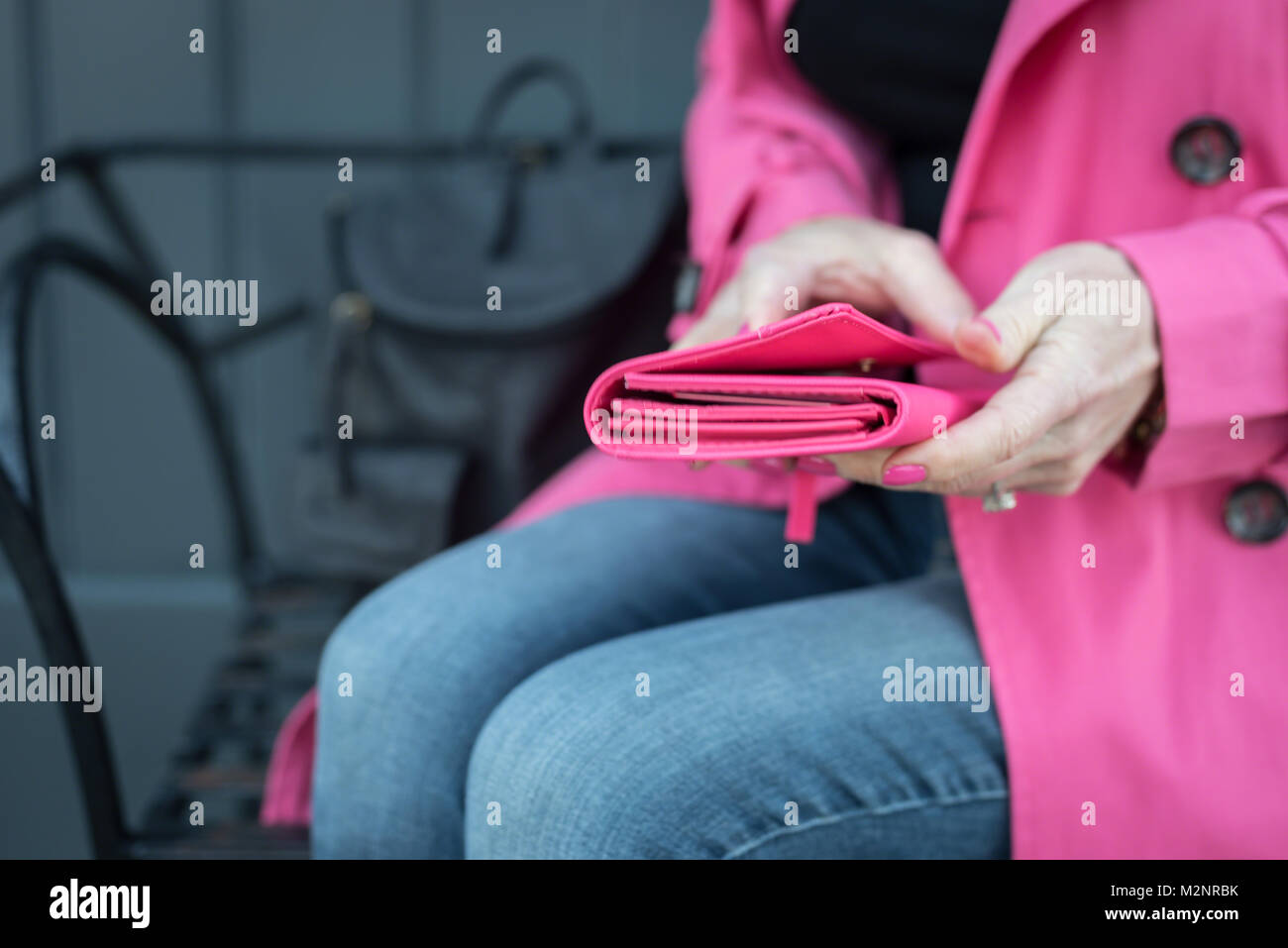 woman sitting on bench wearing coordinating pink coat, wallet and nail polish - Stock Image