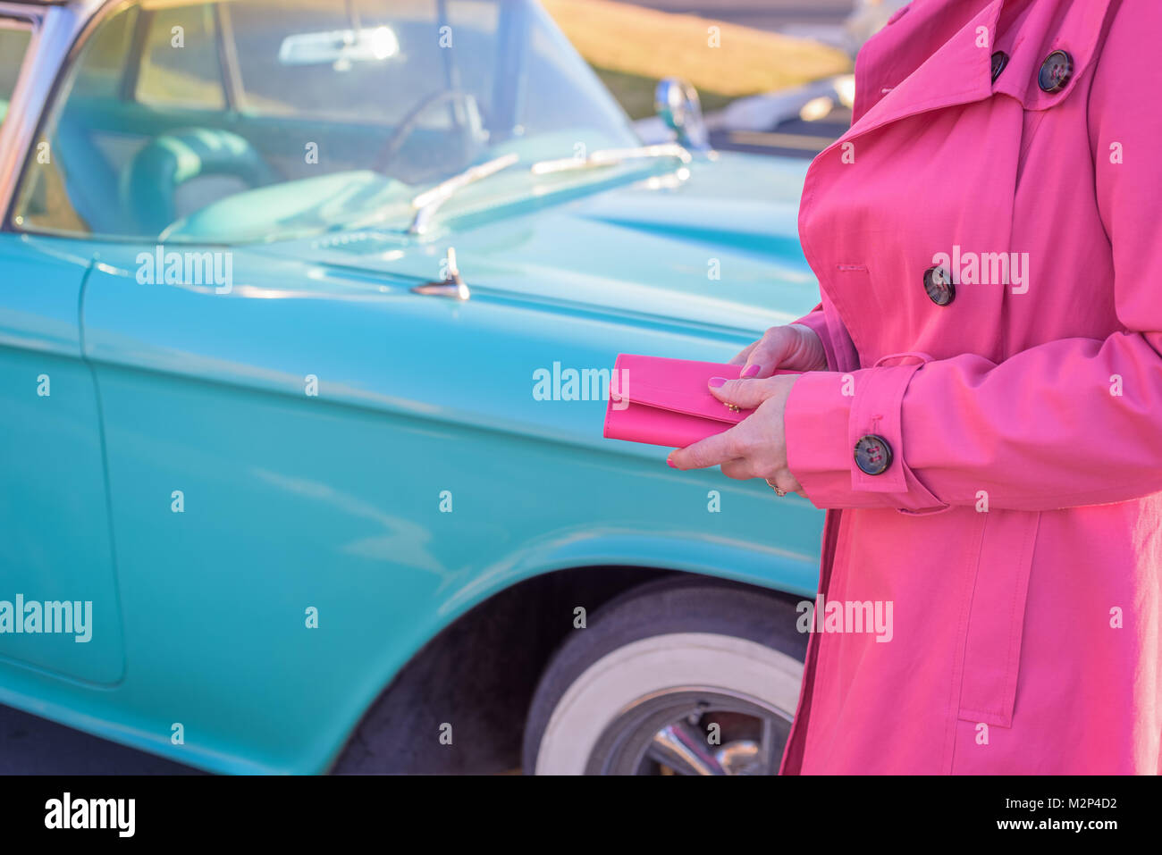 woman in hot pink coat holding wallet looking at baby blue classic car Stock Photo