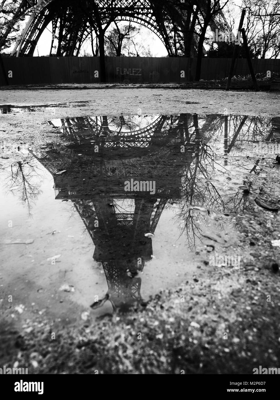 Eiffel Tower reflected in a puddle after a violent storm. - Stock Image