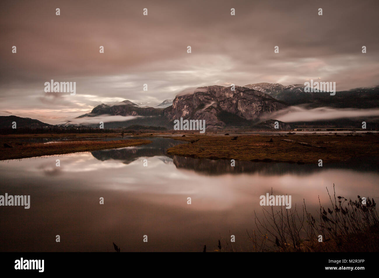 The Squamish Estuary at sunrise during a king tide. The Stawamus Chief is in the background with a colourful and - Stock Image