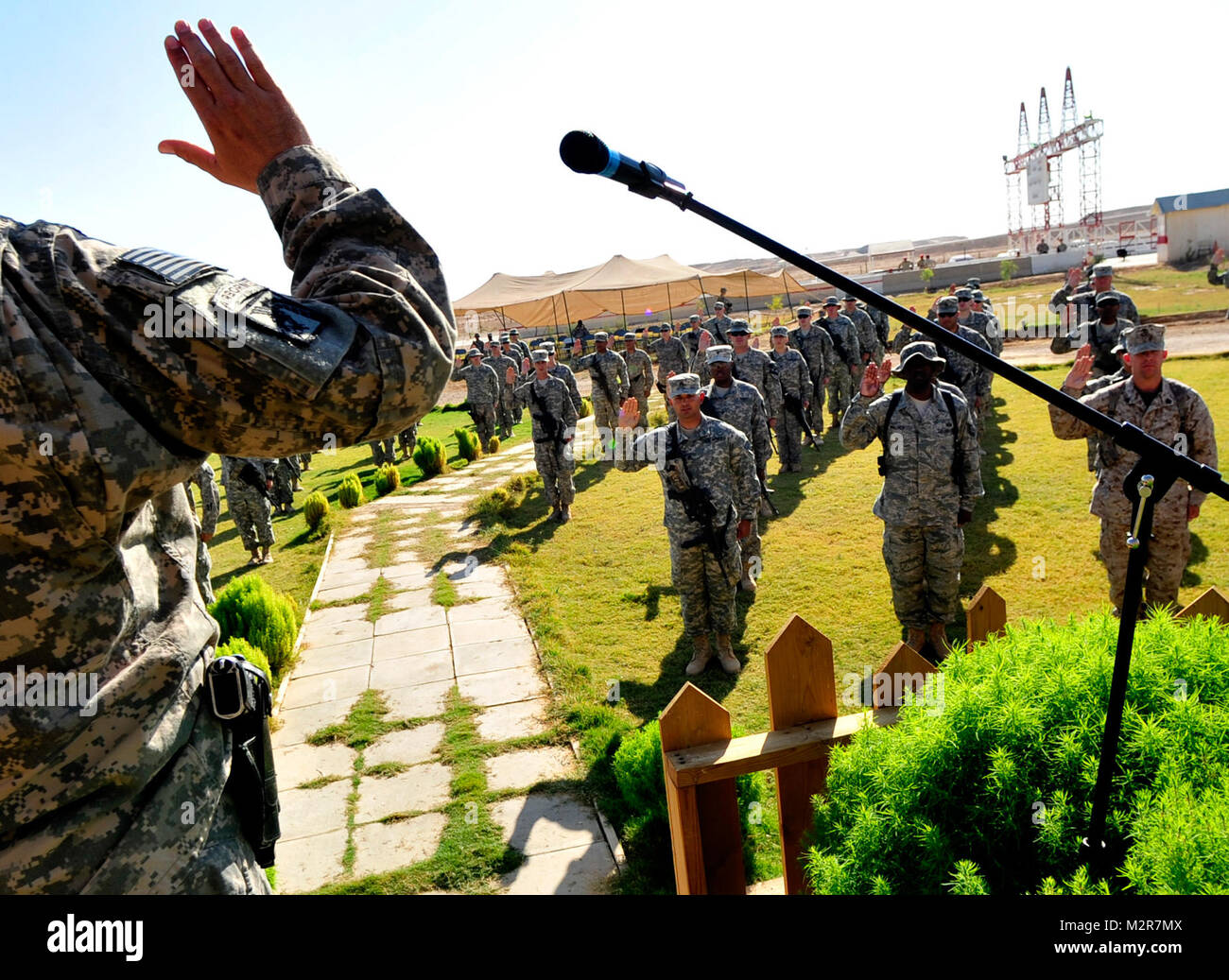 With right hands raised, 126 U.S. service members rehearse prior to a mass re-enlistment ceremony at Al Asad Air Stock Photo