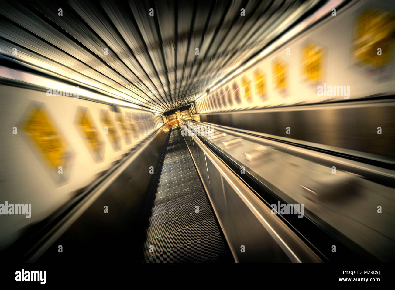 Moving stairs to the underground train tunnel, blur, vanishing point perspective - Stock Image