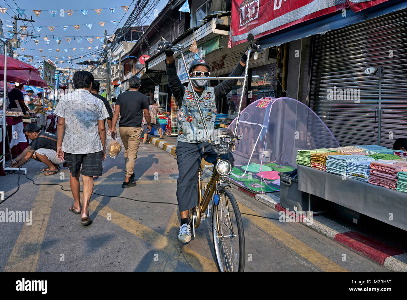 Young man riding a highly modified bicycle resembling a chopper motorcycle with raised handlebars. Thailand Southeast - Stock Image