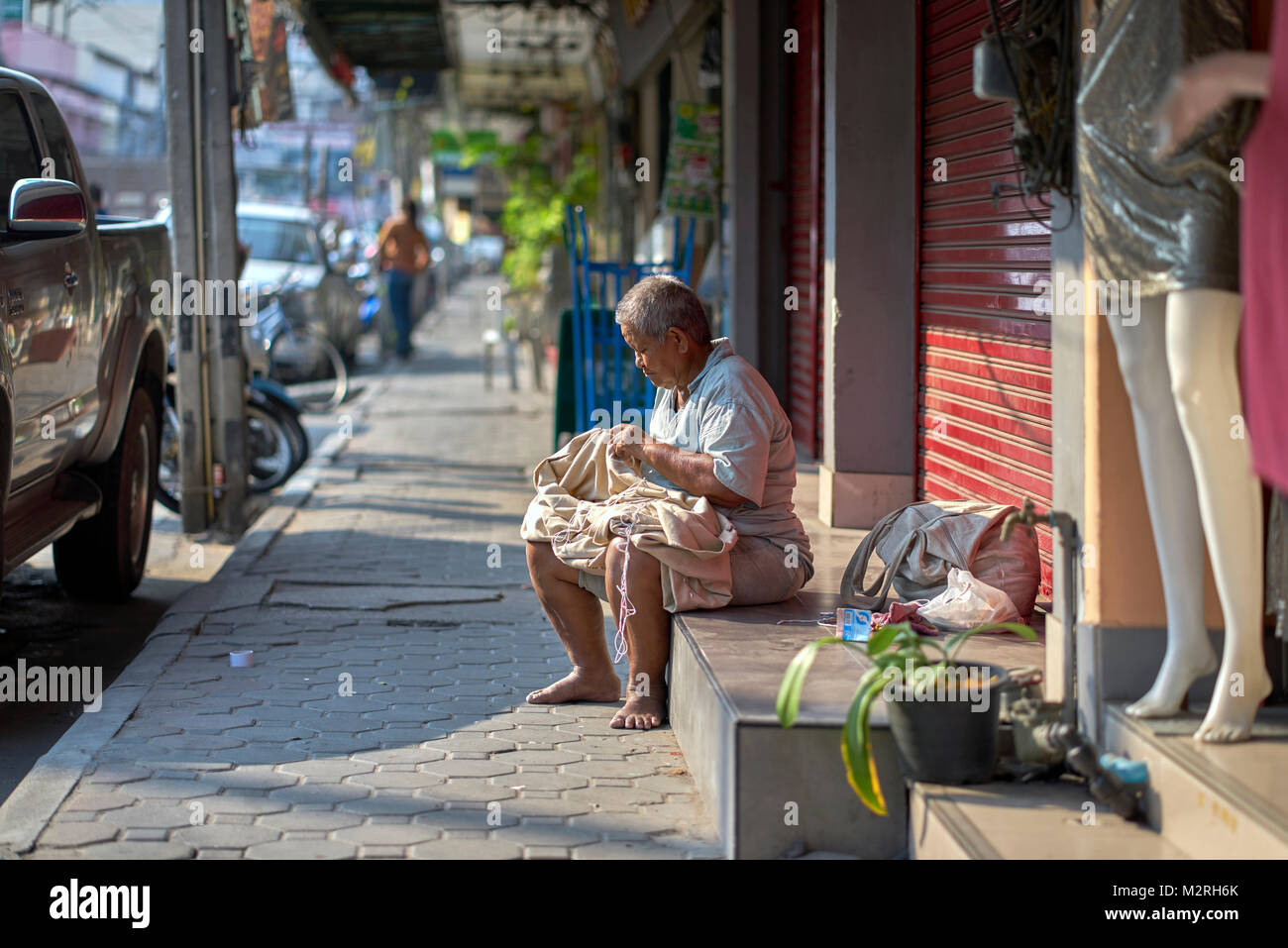 Elderly Thai woman, barefeet in the street, sowing sacks for local shops. Thailand poverty, Southeast Asia - Stock Image