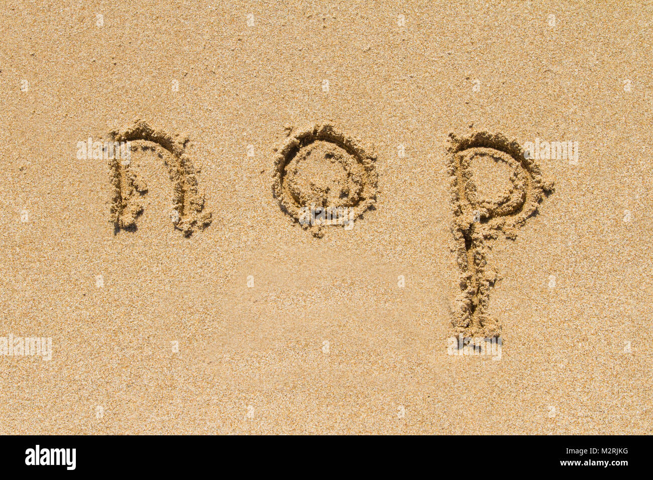 Set of nop letters of alphabet written on sand with lower case. - Stock Image