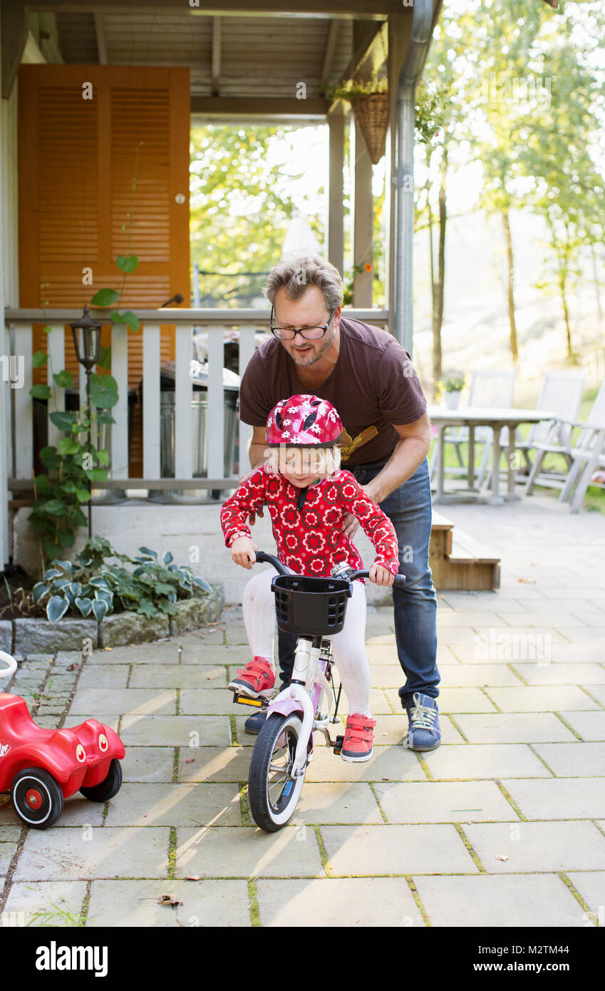 Man teaching his daughter to ride bicycle in Sweden - Stock Image