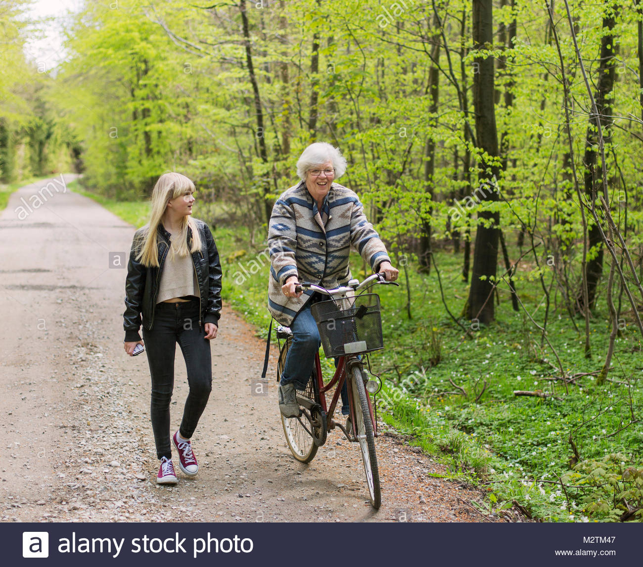 Grandmother and granddaughter with bicycle on forest road - Stock Image