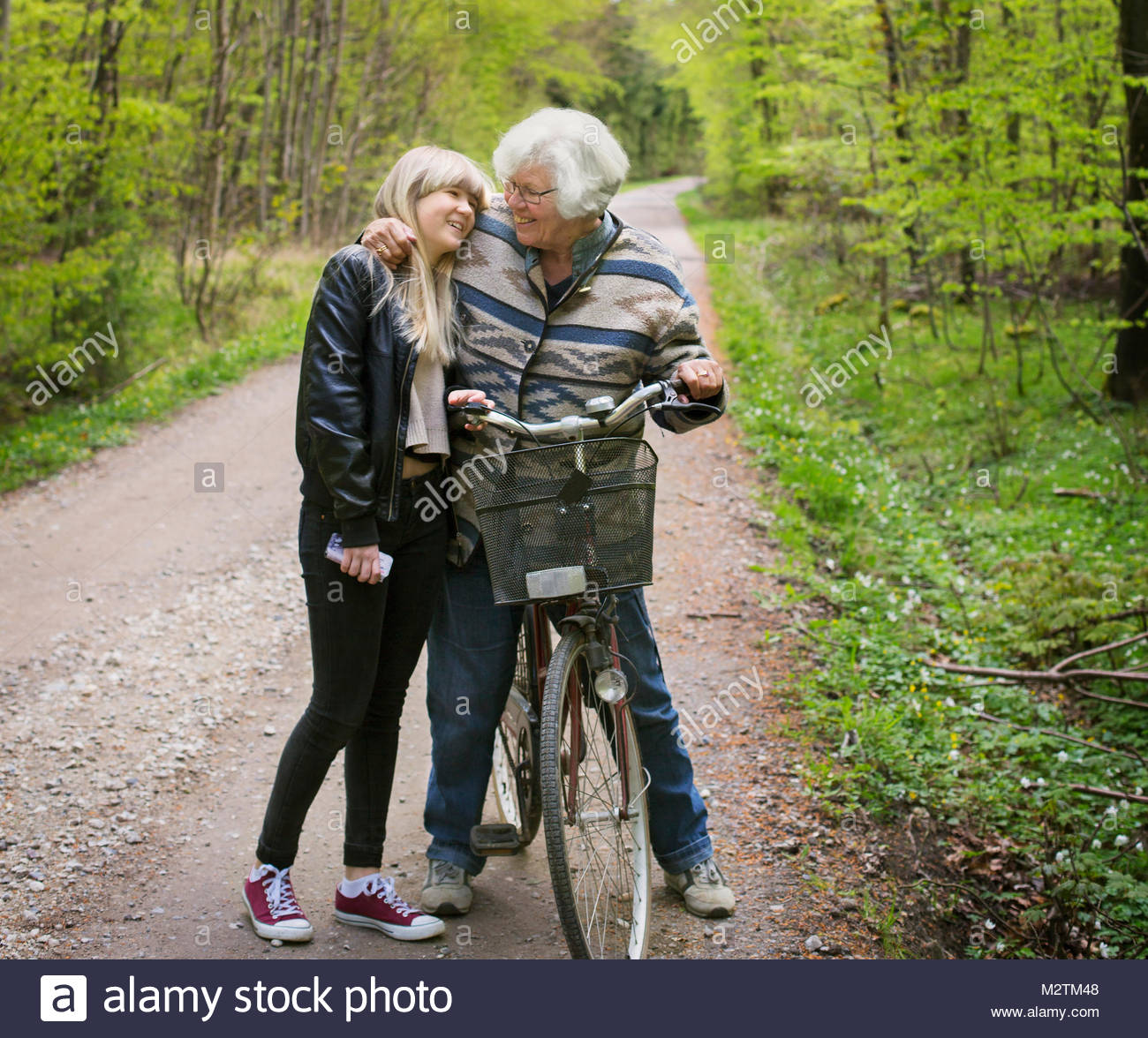 Grandmother and granddaughter embracing on forest road - Stock Image