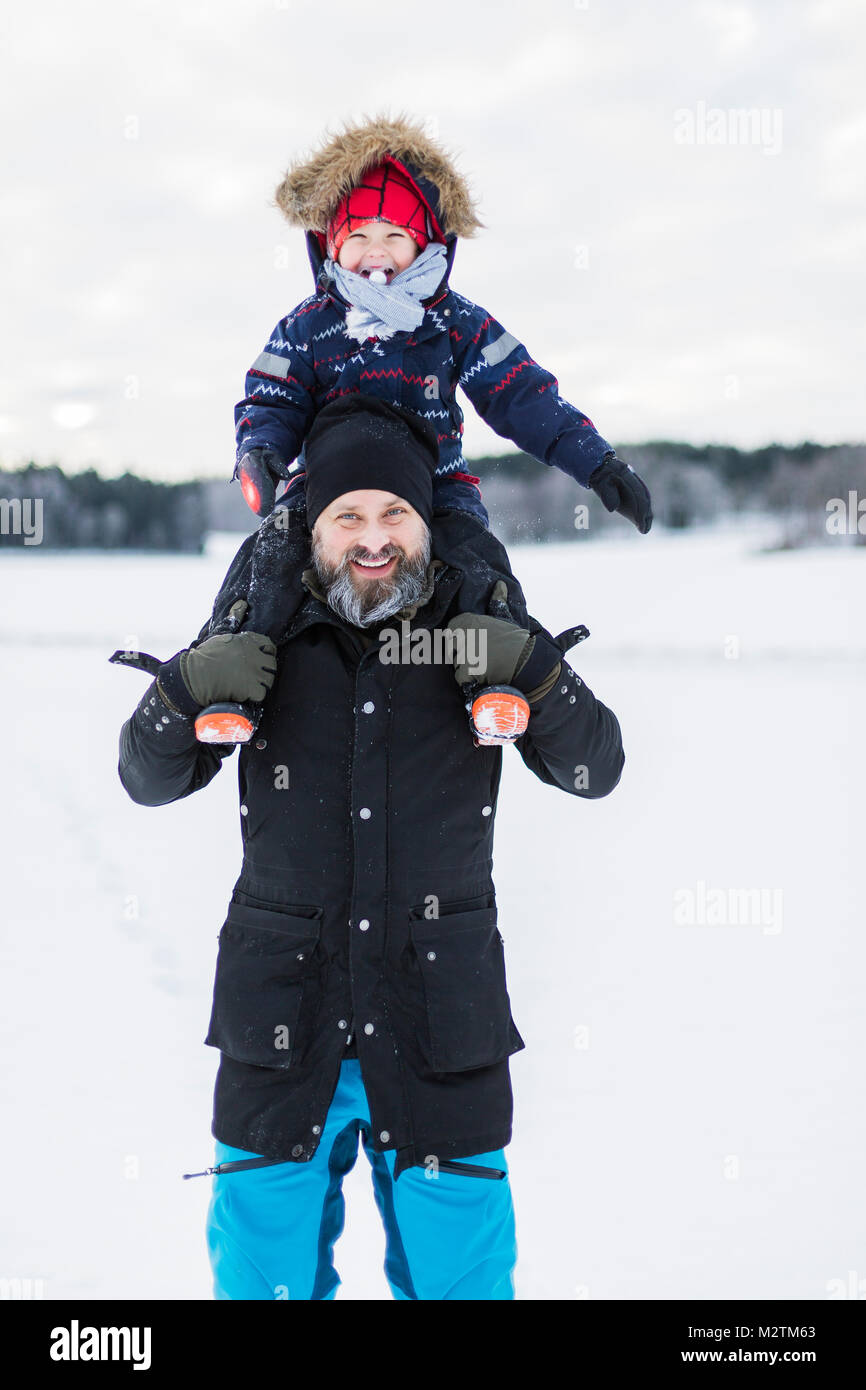 Son of fathers shoulders in snow - Stock Image