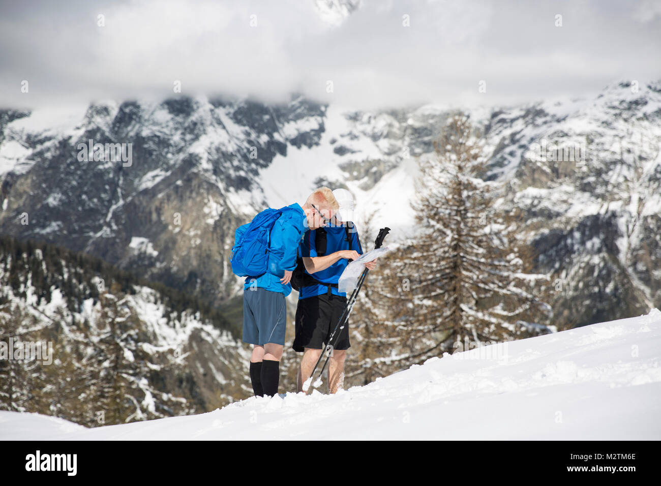 Men looking at a map during a hike up a mountain in Courmayeur, Italy - Stock Image