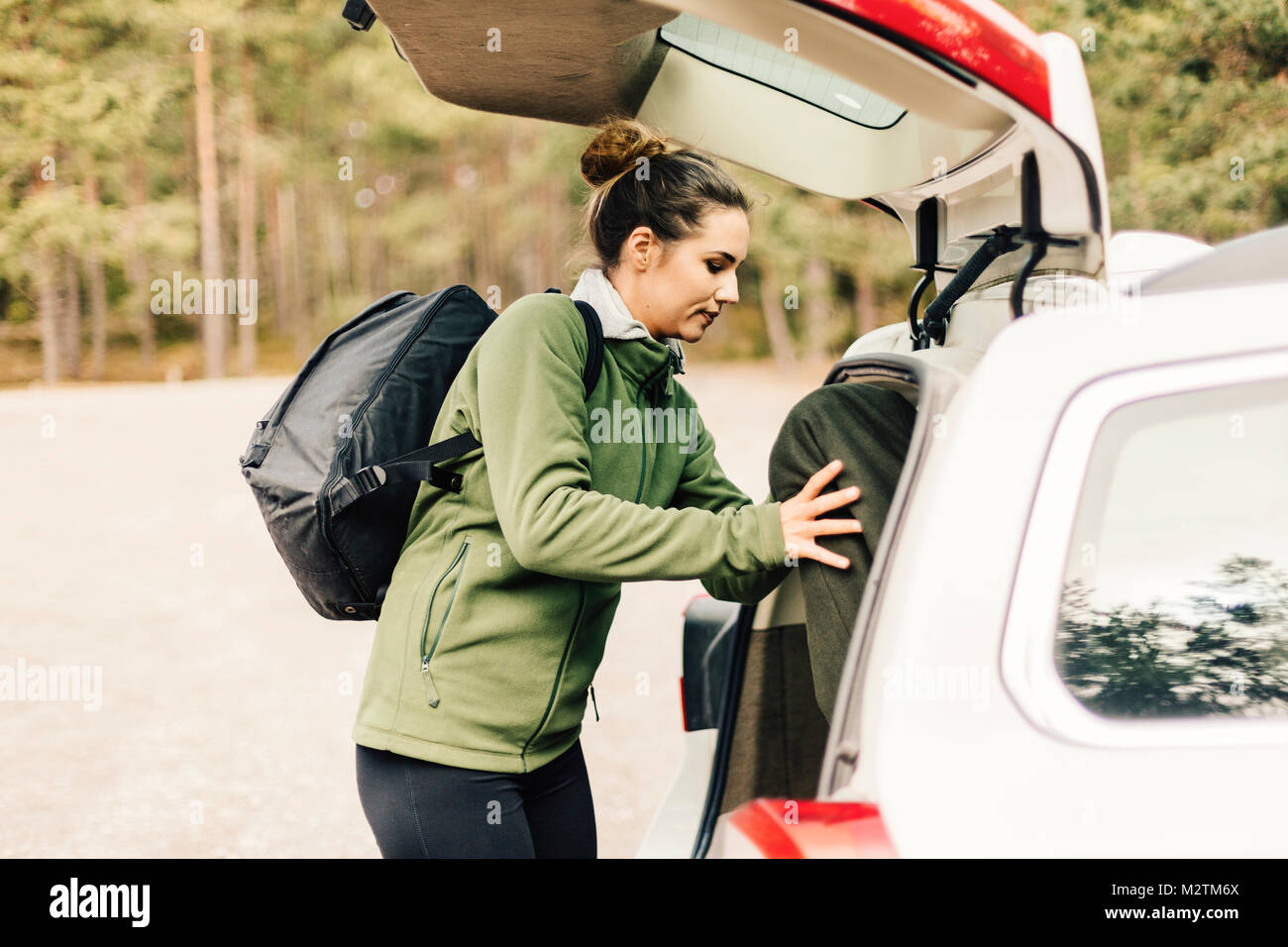 Woman loading bags in car in Sodermanland, Sweden - Stock Image