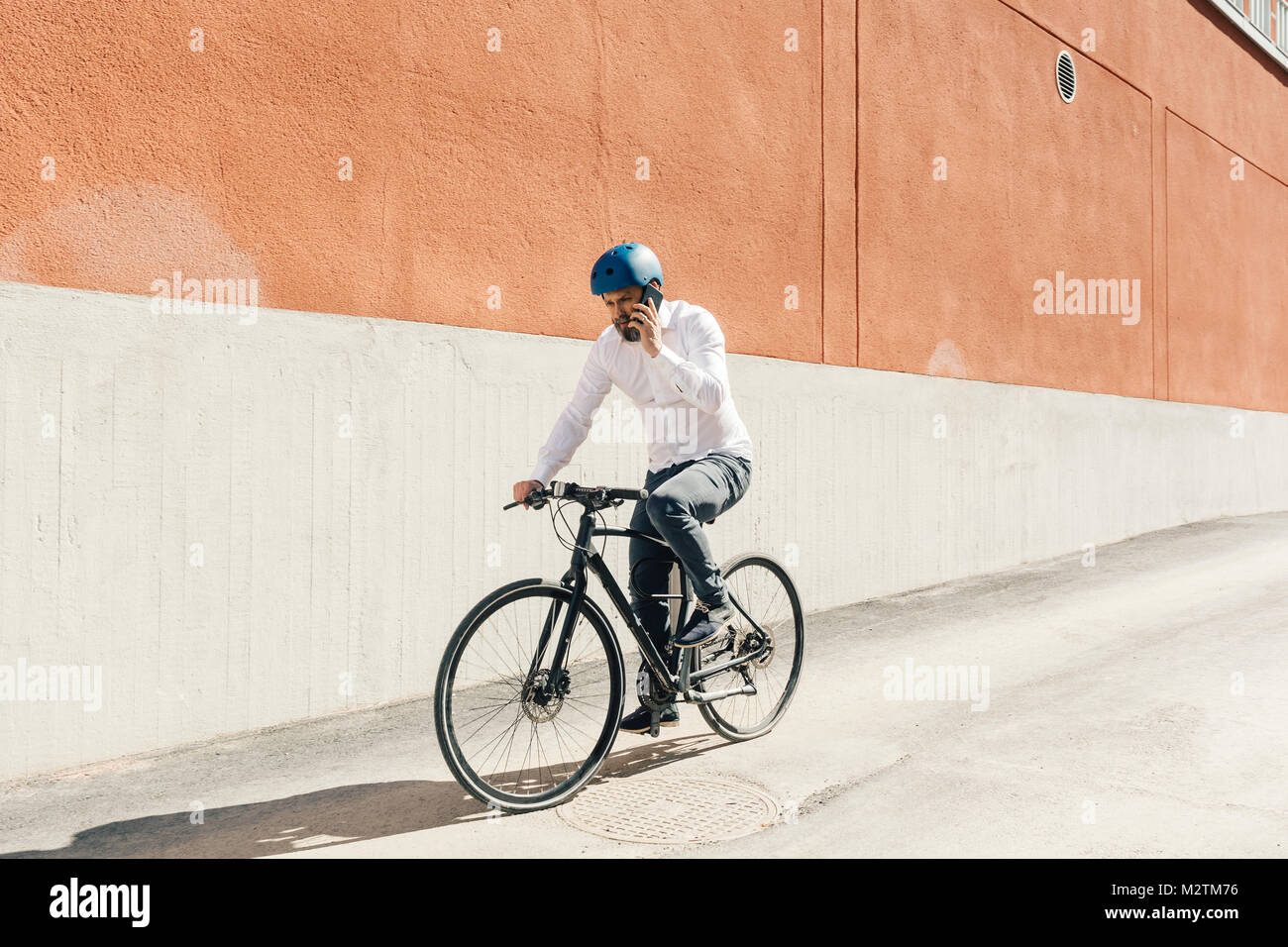 Man on smart phone while bicycling in Sweden - Stock Image