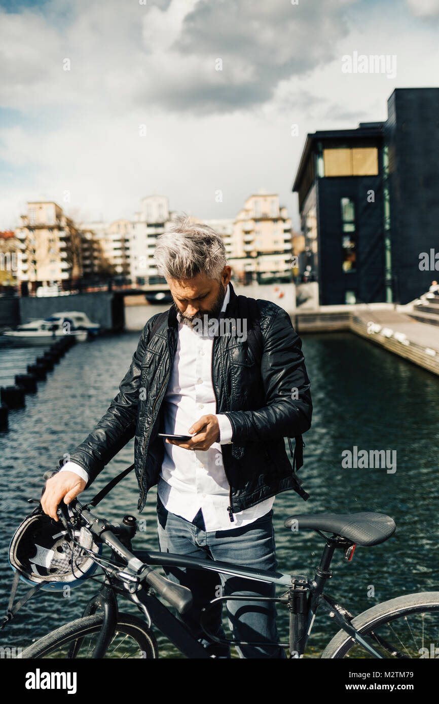 Man on smart phone with bicycle in Stockholm, Sweden - Stock Image