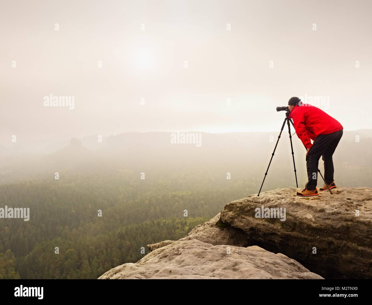 Hiker with camera on tripod takes picture from rocky summit. Alone photographer at edge photograph misty landscape, - Stock Image
