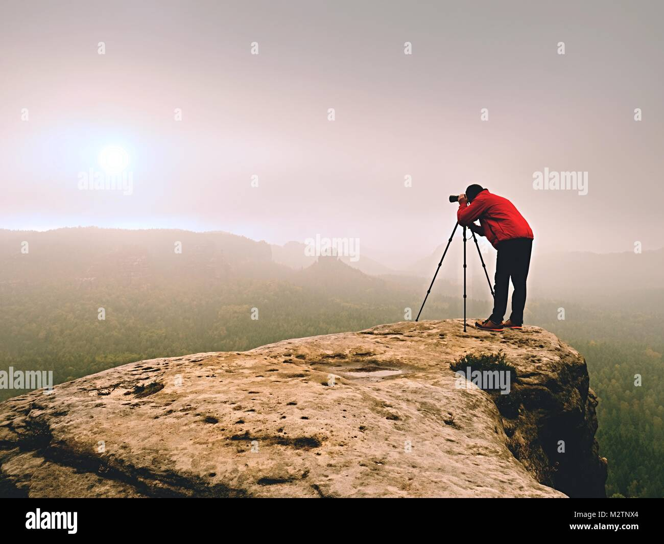 Professional photographer shooting. Artist stay  with tripod on summit and  takes pictures of autumnal coutryside. - Stock Image