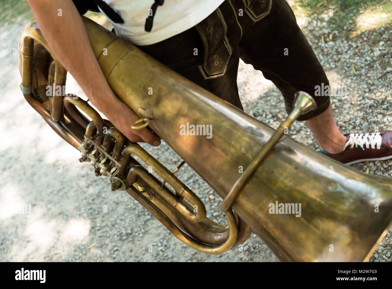 Man wearing Lederhosen, with tuba, detail - Stock Image
