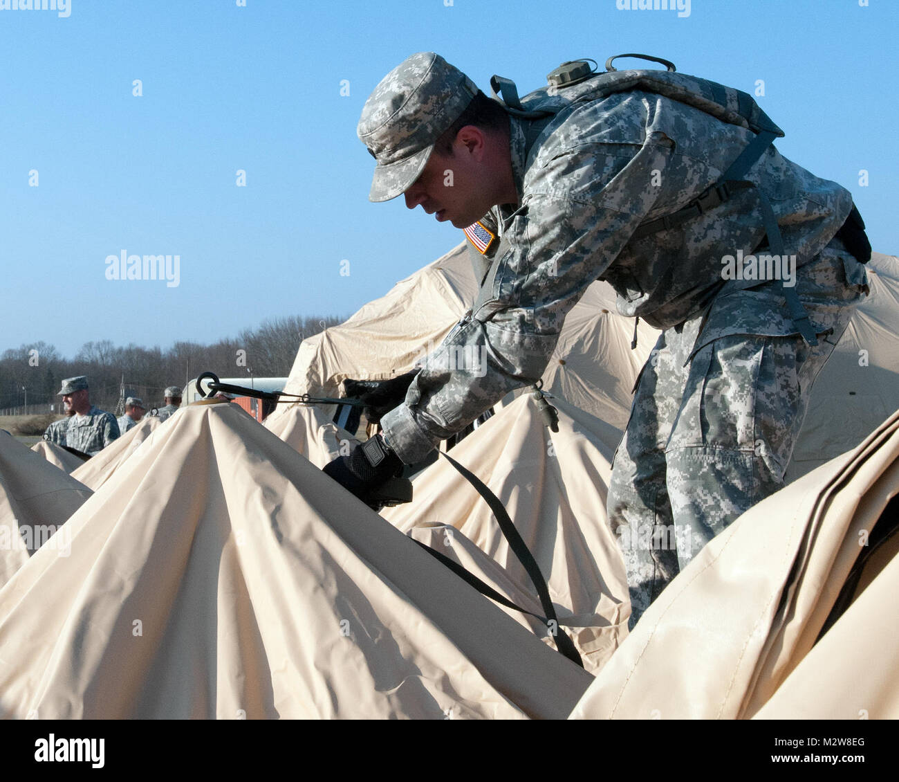 Spc. Jonathan Carey, a member of the 316th ESC and a native of Freedom, Pa., connects a tie down line to the roof - Stock Image