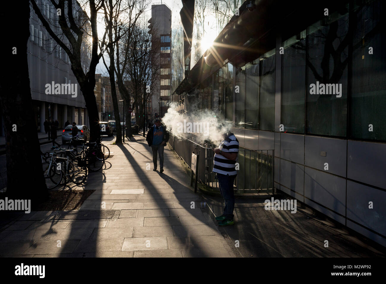 A vaper exhales a cloud of smoke in bright winter sunlight, on a central London street, on 6th February 2018, in - Stock Image