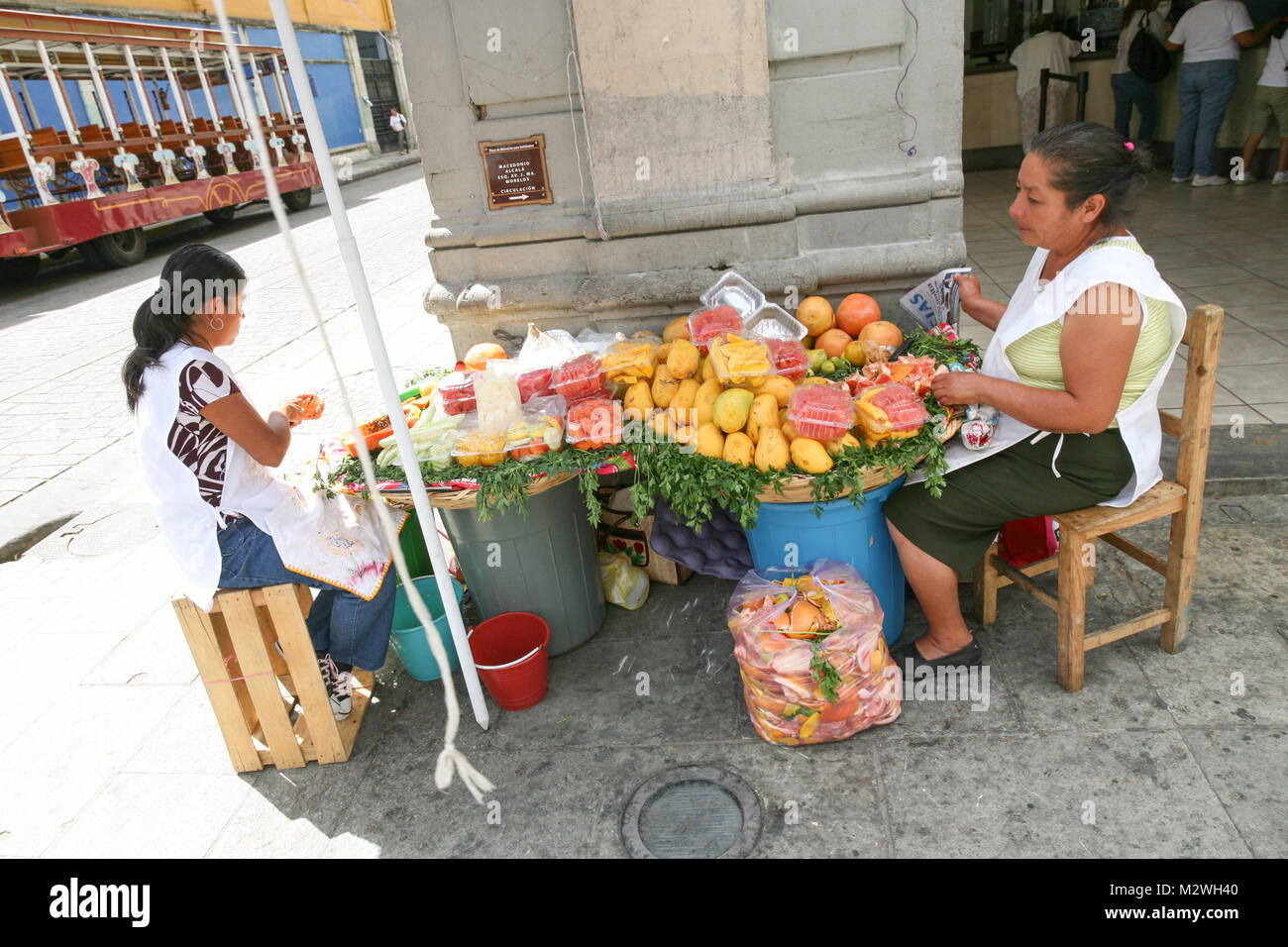 OAXACA, MEXICO - MARCH 7th, 2012: Women selling fresh fruits and juices on a  central  street in  Oaxaca city, Mexico Stock Photo