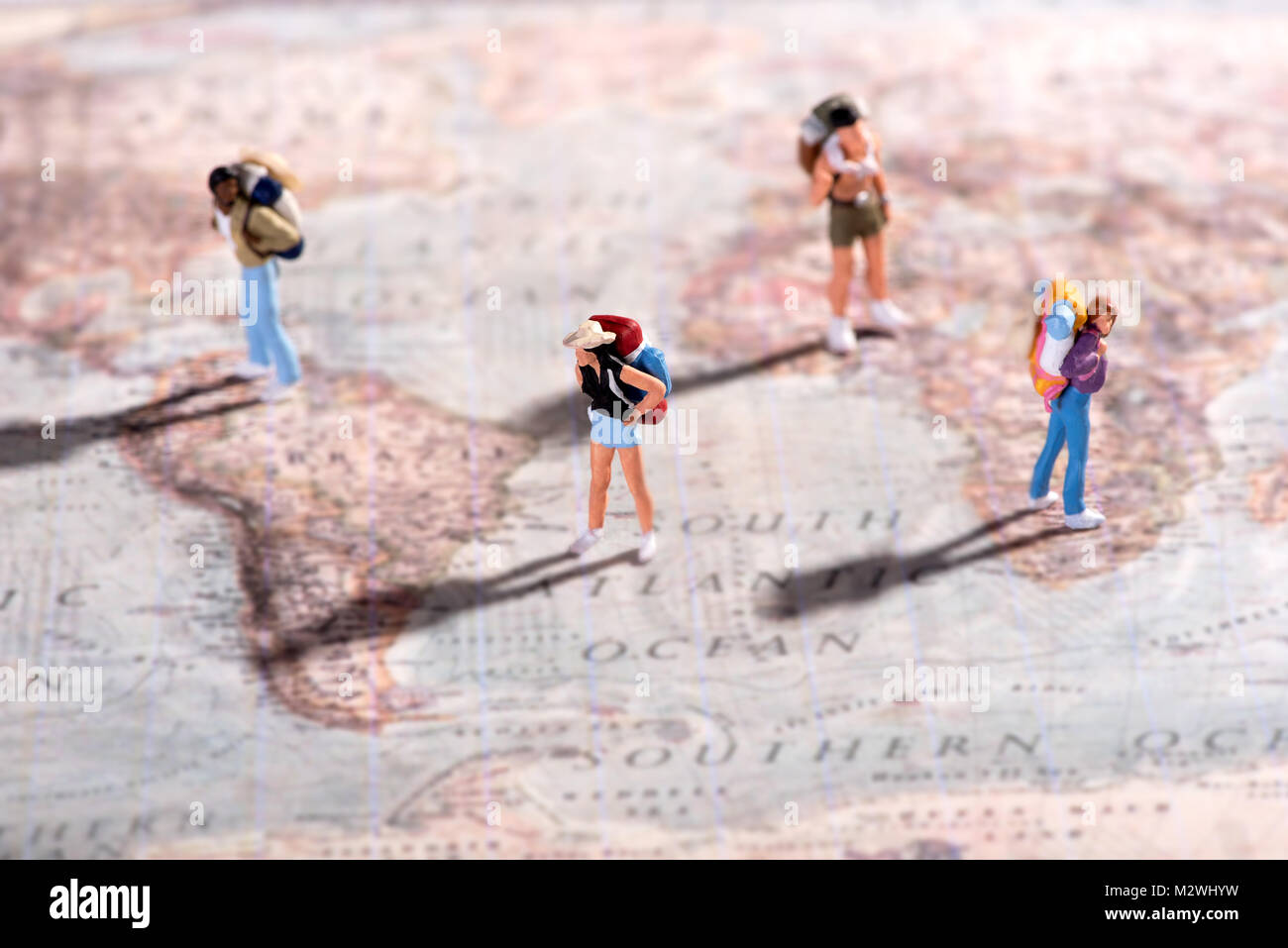 Group of young travellers miniature people figurines with backpacks on a world map standing on assorted destinations - Stock Image