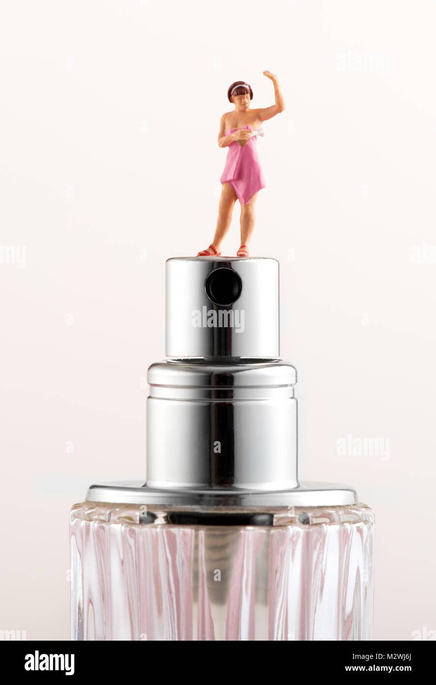 Miniature woman with a towel wrapped round her on top of the atomiser of a scent bottle in a concept of personal - Stock Image