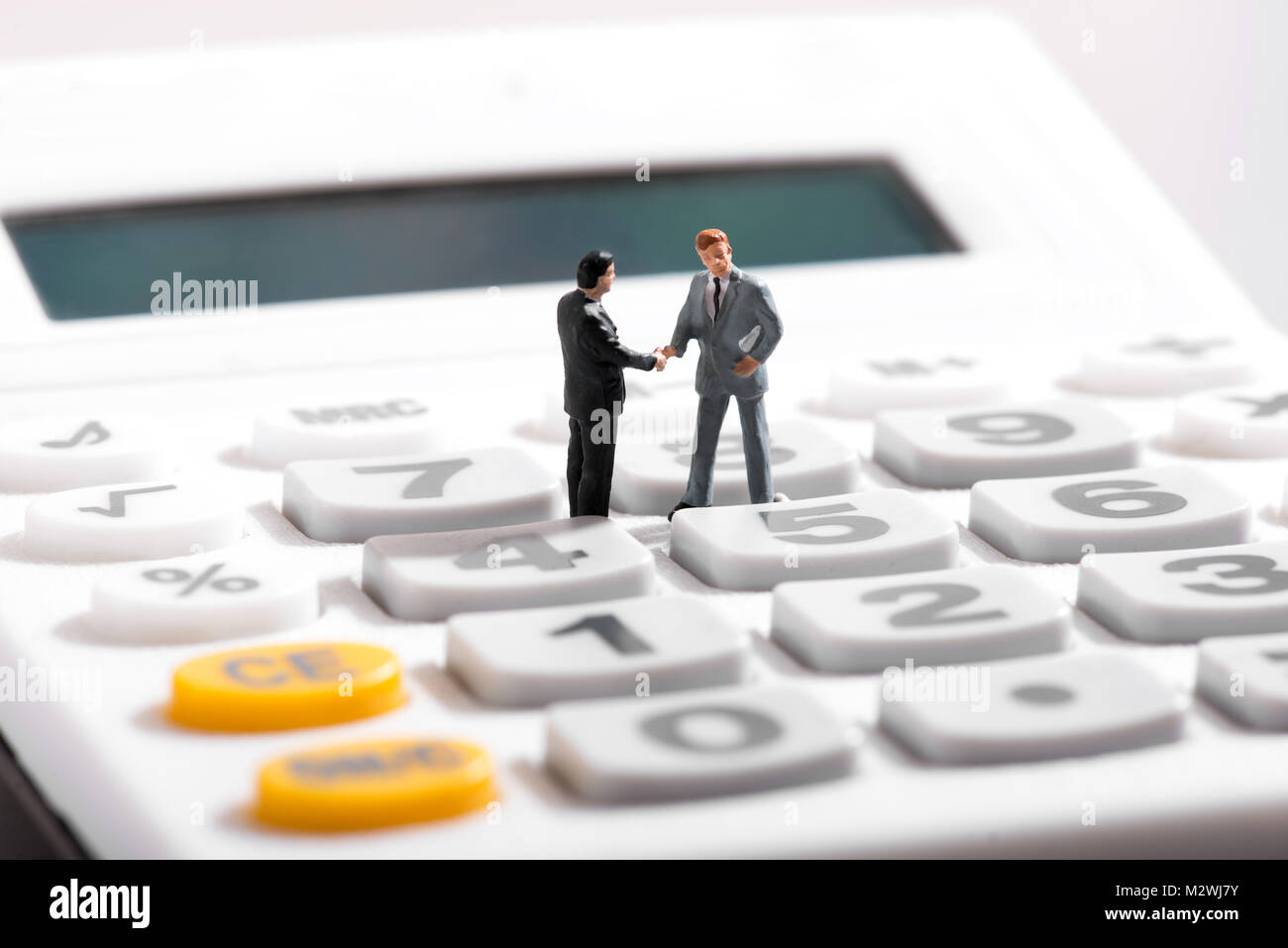 Business concept with two figurines of businessmen standing on calculator - Stock Image