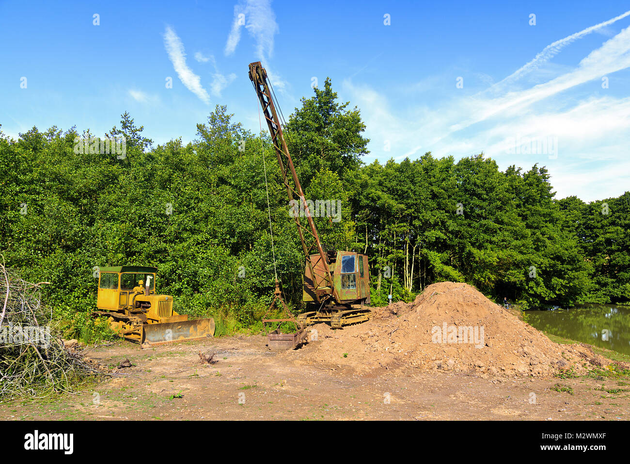 Old Bulldozer and Crane used for dredging lake - Stock Image